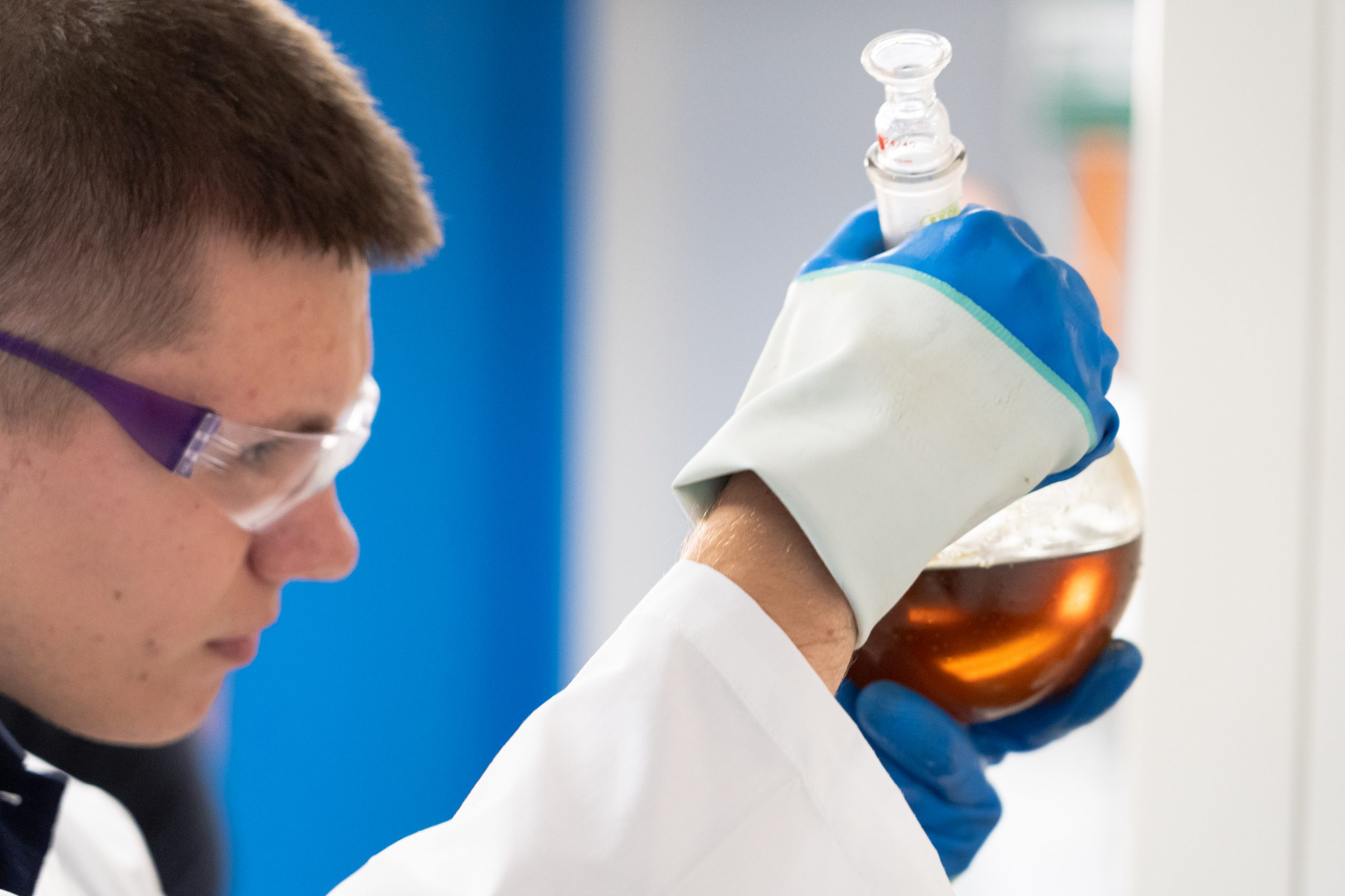 a chemist examining chemicals in a flask