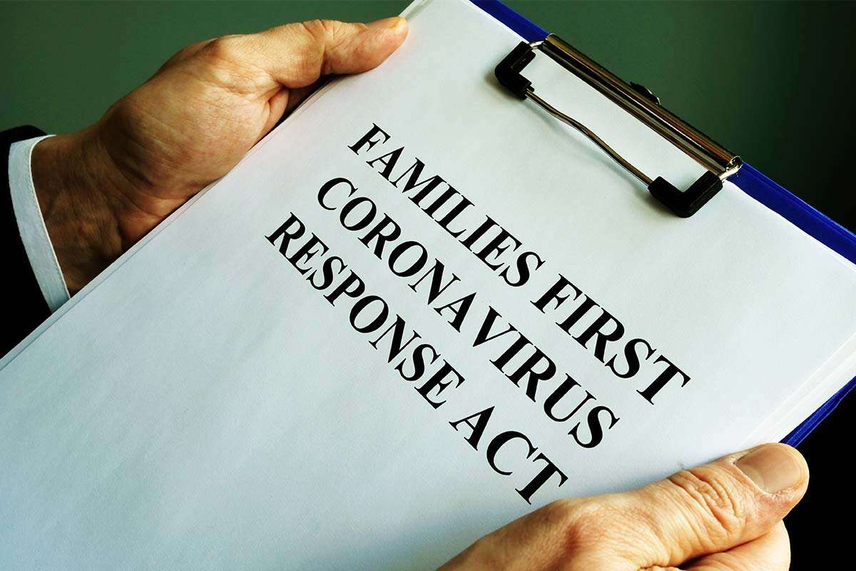 a clipboard with a printout of the Families First Coronavirus Response Act